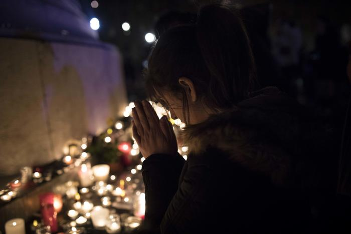 A woman pays respect at Republic square in Paris, France, Sunday, Nov. 13, 2016. France marked the anniversary of Islamic extremists' coordinated attacks on Paris with a somber silence on Sunday that was broken only by voices reciting the names of the 130 slain, and the son of the first person to die stressing the importance of integration. (ANSA/AP Photo/Kamil Zihnioglu) [CopyrightNotice: Copyright 2016 The Associated Press. All rights reserved.]