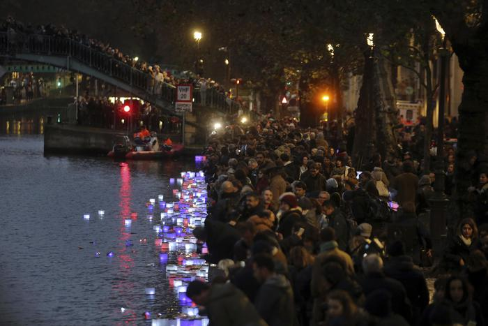 People light candles by the Saint Martin canal, near the restaurant Le Petit Cambodge (Little Cambodia) and the Carillon Hotel in Paris, Sunday, Nov. 13, 2016. France marked the anniversary of Islamic extremists' coordinated attacks on Paris with a somber silence on Sunday that was broken only by voices reciting the names of the 130 slain, and the son of the first person to die stressing the importance of integration. (ANSA/AP Photo/Thibault Camus) [CopyrightNotice: Copyright 2016 The Associated Press. All rights reserved.]